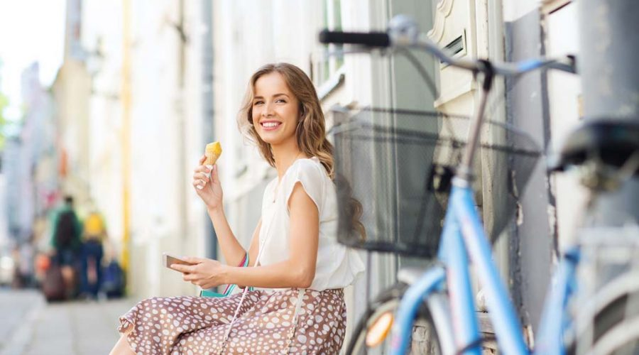 happy woman with smartphone, bike and ice cream