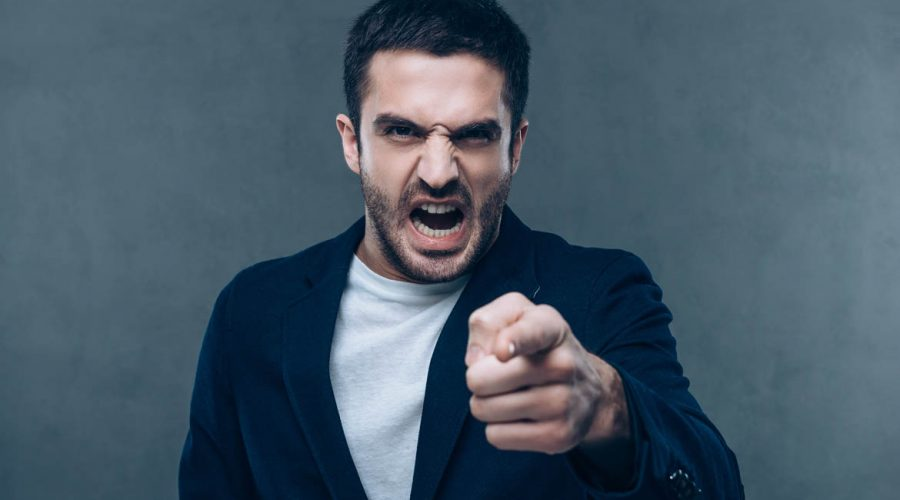 Furious young man looking at camera and pointing you while standing against grey background